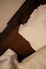 Vacker gammal dörr agerar sänggavel bakom krispigt vitt sänglinne