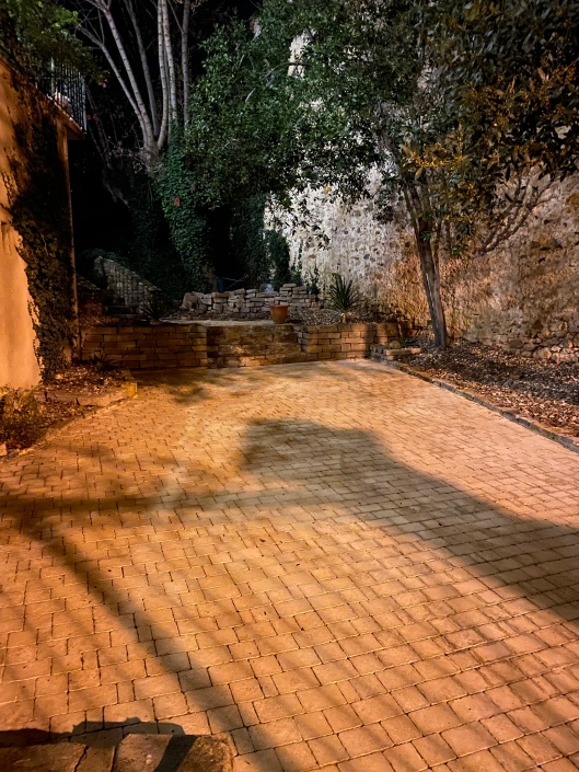 Lövblåst och renspolad stenläggning i kvällsljus